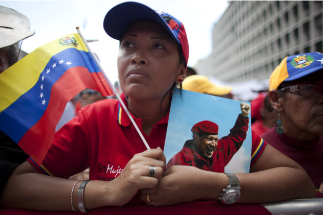 "A woman holds a picture of Venezuela's President Hugo Chavez and the country's national flag during an event commemorating the violent street protests of 1989 known as the ""Caracazo,""  in Caracas, Ven"
