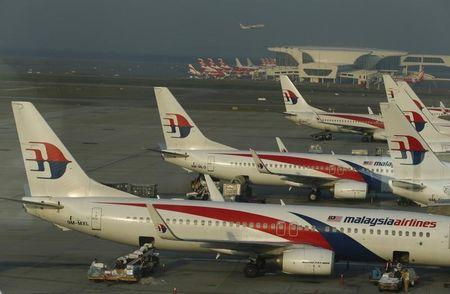 Ground crew work among Malaysia Airlines planes on the runway at Kuala Lumpur International Airport (KLIA) in Sepang