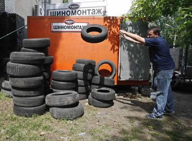 An employee tosses tyres at a tyre service shop in Kiev