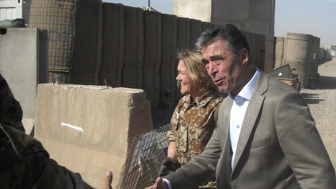 NATO Secretary-General Anders Fogh Rasmussen, rights, greets soldiers as he tours the ISAF headquarters Task Force Helmand, Tuesday, March 5, 2013. NATO's chief is embracing a proposal to keep 352,000 Afghans in uniform through 2018 — about 122,000 more than originally planned. (AP Photo/Kimberly Dozier)