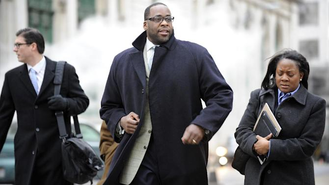 CORRECTS SPELLING OF DERRICK IN SECOND SENTENCE - Kwame Kilpatrick, center, heads to federal court in Detroit on Monday Monday Jan. 7, 2013.  Derrick Miller, a longtime confidant of the former Detroit mayor, testified against Kilpatrick at his corruption trial Monday telling jurors he passed thousands of dollars to Kilpatrick from a contractor at the city's convention center. Kilpatrick resigned as mayor in 2008. Miller pleaded guilty to corruption in 2011 and agreed to cooperate with prosecutors. (AP Photo/Detroit News,David Coates )  DETROIT FREE PRESS OUT; HUFFINGTON POST OUT