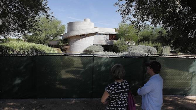In this photo taken Wednesday, Oct. 3, 2012, concerned citizens take a look at a 1952 Frank Lloyd Wright-designed home in the Arcadia neighborhood of Phoenix. The city of Phoenix and a developer who was poised to demolish the home have reached an agreement that will put any work on hold while a search continues for a buyer, a city official confirmed Wednesday. (AP Photo/Ross D. Franklin)