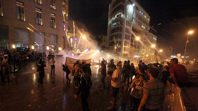 Fireworks set off by protesters are pictured as security forces use water cannons in Martyr square, downtown Beirut