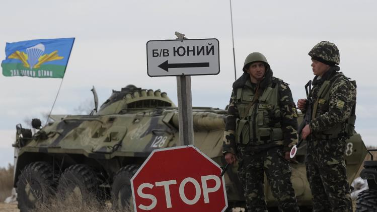 Ukrainian servicemen guard a checkpoint near the village of Strelkovo