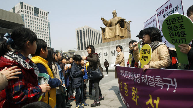 """An unidentified elementary school teacher, center, orders her students to leave as they watch South Korean housewives stage a press conference denouncing the annual joint military exercise known as Foal Eagle, between South Korea and the United States, near the U.S. Embassy in Seoul, South Korea, Monday, April 8, 2013. South Korea's top security official said Sunday that North Korea may be setting the stage for a missile test or another provocative act with its warning that it soon will be unable to guarantee diplomats' safety in Pyongyang. But he added that the North's clearest objective is to extract concessions from Washington and Seoul. The writing on the banner reads """" Peace.""""(AP Photo/Ahn Young-joon)"""