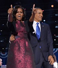US President Barack Obama and First Lady Michelle Obama acknowledge supporters following Obama's victory speech in Chicago