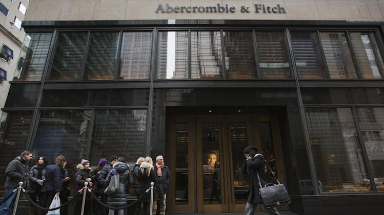 A pedestrian walks past shoppers lined up to wait for the opening of an Abercrombie & Fitch store in New York