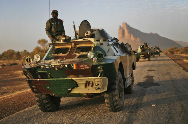 A convoy of Malian troops makes a stop to test some of their weapons near Hambori, northern Mali, on the road to Gao, Monday Feb. 4, 2013. French troops launched airstrikes on Islamic militant training camps and arms depots around Kidal and Tessalit in Mali's far north, defense officials said Sunday, as the first supply convoy of food, fuel and parts to eastern Mali headed across the country.(AP Photo/Jerome Delay)