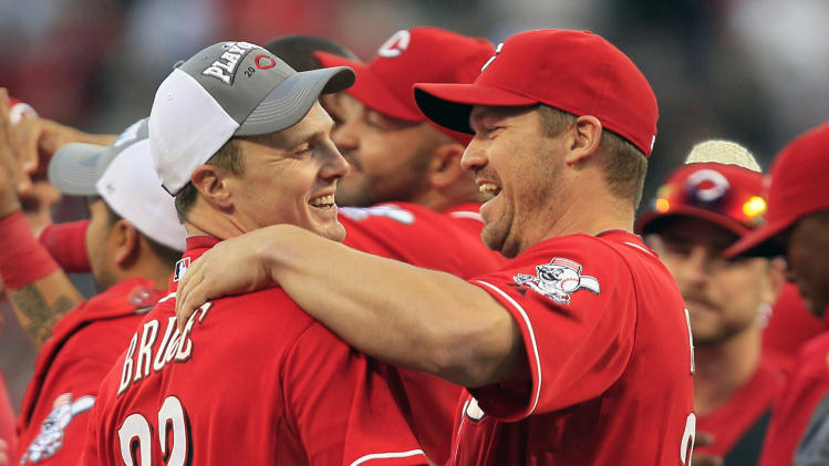 Cincinnati Reds' Jay Bruce (32) hugs teammate Scott Rolen after they defeated the Los Angeles Dodgers 6-0 to clinch the National League Central Division in a baseball game on Saturday, Sept. 22, 2012, in Cincinnati. (AP Photo/Al Behrman)