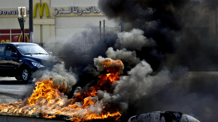 Vehicles pass by tires and old water storage tanks set on fire by Bahraini anti-government protesters in Malkiya, Bahrain, Monday, Dec. 17, 2012. Pro-democracy protests continue in villages around the Gulf island kingdom. (AP Photo/Hasan Jamali)