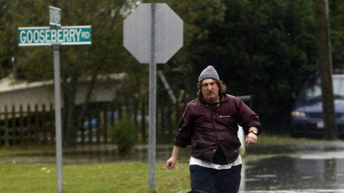 A man walks down a flooded street as Hurricane Sandy approaches, Monday, Oct. 29, 2012, in Mastic Beach, N.Y.  Hurricane Sandy continued on its path Monday, forcing the shutdown of mass transit, schools and financial markets, sending coastal residents fleeing, and threatening a dangerous mix of high winds and soaking rain. (AP Photo/Jason DeCrow)