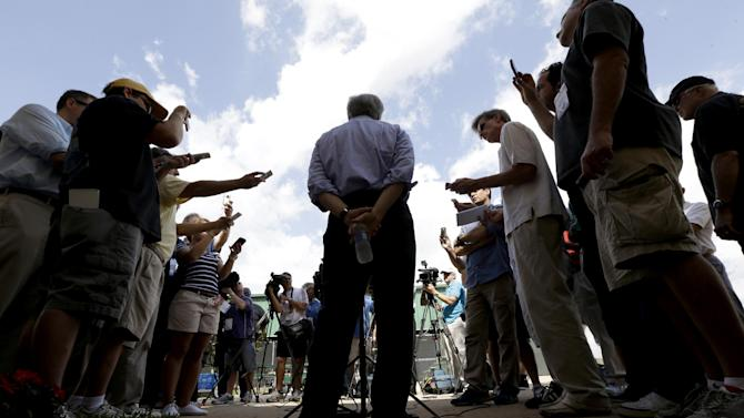 Miami Marlins owner Jeffrey Loria, center, talks during a news conference outside of the team's spring training facility before an exhibition spring training baseball game against the New York Mets, Tuesday, Feb. 26, 2013, in Jupiter, Fla. (AP Photo/Julio Cortez)