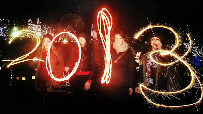 Katy Saunders, left, Alex Mueller, center left, Rebekka Frank and Arina Motamedi, right, play with sparklers ahead of welcoming in the new year during the 2013 Edinburgh Hogmanay celebrations, Scotland, Monday December 31, 2012. See PA story SOCIAL NewYear. (AP Photo/PA,Danny Lawson)UNITED KINGDOM OUT