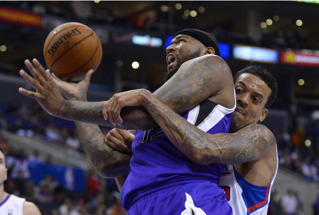 Sacramento Kings center DeMarcus Cousins, left, is fouled by Los Angeles Clippers small forward Matt Barnes as he goes up for a shot during the second half of their NBA basketball game, Friday, Oct. 2