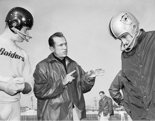 In this Dec. 18, 1963 file photo, Al Davis, center, head coach of the American Football League's Oakland Raiders, talks with players at the team's home practice field in Oakland, Calif. Davis, the Hal