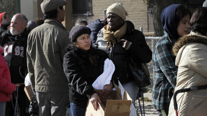 A woman holds a box of food she picked up at an American Red Cross station in the Coney Island section of Brooklyn, Monday, Nov. 5, 2012 in New York. The region is still cleaning up a week after Superstorm Sandy. (AP Photo/Mark Lennihan)