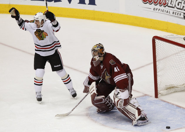 Chicago Blackhawks' Dave Bolland celebrates a game-winning goal by teammate Bryan Bickell as Phoenix Coyotes' Mike Smith (41) stands in front of the goal during overtime in Game 2 of an NHL hockey Sta