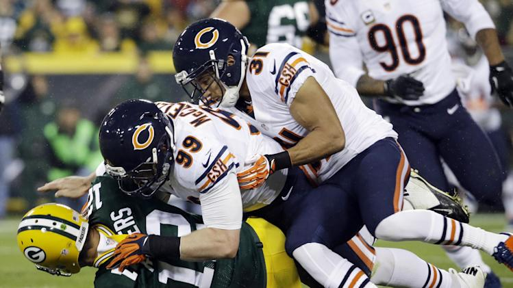 Green Bay Packers quarterback Aaron Rodgers is sacked by Chicago Bears' Shea McClellin (99) and Isaiah Frey (31) during the first half of an NFL football game Monday, Nov. 4, 2013, in Green Bay, Wis. (AP Photo/Morry Gash)