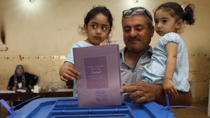 An Iraqi man, holding his two daughters, casts his ballot at a polling center in Basra, Iraq, 550 kilometers (340 miles) south of Baghdad, Iraq, Saturday, April 20, 2013. Polls opened amid tight security in Iraq on Saturday for regional elections in the country's first vote since the U.S. military withdrawal, marking an important test of the country's stability. (AP Photo/Nabil Al-Jurani)