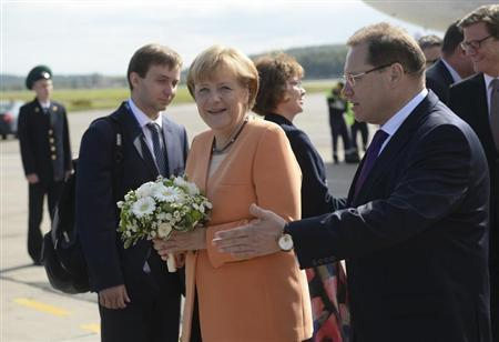 German Chancellor Angela Merkel receives flowers as she arrives to take part in the G20 Summit in St. Petersburg