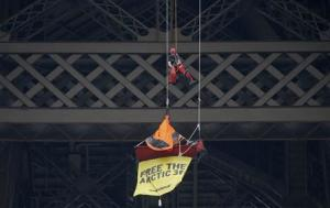 A French firefighter approaches a Greenpeace activist hanging from the second floor of the Eiffel Tower in Paris