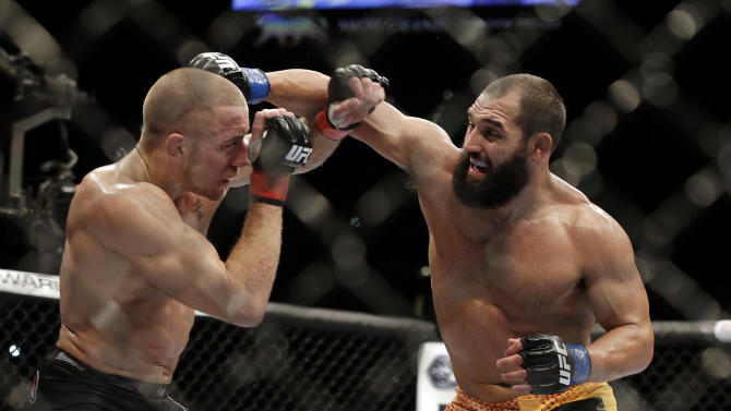 Johny Hendricks, right, exchanges punches with Georges St. Pierre, of Canada, during a UFC 167 mixed martial arts championship welterweight bout on Saturday, Nov. 16, 2013, in Las Vegas. St. Pierre won by split decision. (AP Photo/Isaac Brekken)