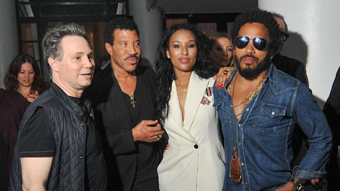 Jason Binn, from left, publisher of DuJour Magazine greets singer song writer Lionel Richie and his girlfriend Lisa Parigi and singer song writer Lenny Kravitz at the annual Art Basel kick off party presented by at the Delano Hotel, Miami Beach on Wednesday, Dec. 2, 2015, in Miami Beach, Fla. (AP Photo/Gaston De Cardenas)