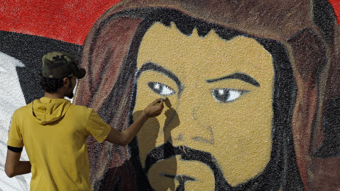 An artist paints a mural on a wall at the airport in Benghazi, Libya,Tuesday, July 5, 2011, portraying the different tribes living in Libya.  (AP Photo/Sergey Ponomarev)