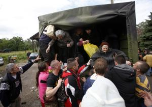People help old women out of a military truck during …