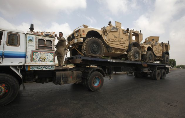 A man stands on a trailer carrying armored vehicles as it drives along a road in Karachi