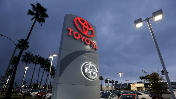 In this Thursday, Nov. 8, 2012, photo, a Toyota dealership signs glows over a car lot in Tustin Calif. A better economy and extra demand after Superstorm Sandy lifted U.S. auto sales in November. (AP Photo/Chris Carlson)
