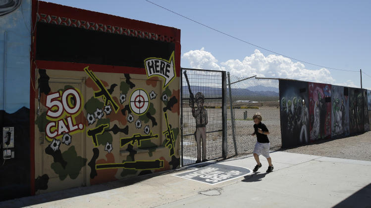 A young person runs by the Last Stop outdoor shooting range Wednesday, Aug. 27, 2014, in White Hills, Ariz. Gun range instructor Charles Vacca was accidentally killed Monday, Aug. 25, 2014 at the range by a 9-year-old with an Uzi submachine gun. (AP Photo/John Locher)