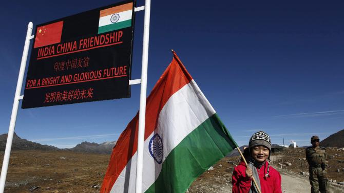 FILE - In this Oct. 21, 2012 file photo, an Indian girl poses for photos with an Indian flag at the Indo China border in Bumla at an altitude of 15,700 feet (4,700 meters) above sea level in Arunachal Pradesh, India. For more than 50 years, it has pitted India against China - a smoldering dispute over who should control a swath of land larger than Austria. Two militaries have skirmished. A brief, bloody war has been fought. And today, thousands of soldiers from both countries sit deployed along their shared frontier, doing little but watching each other. (AP Photo/Anupam Nath, File)