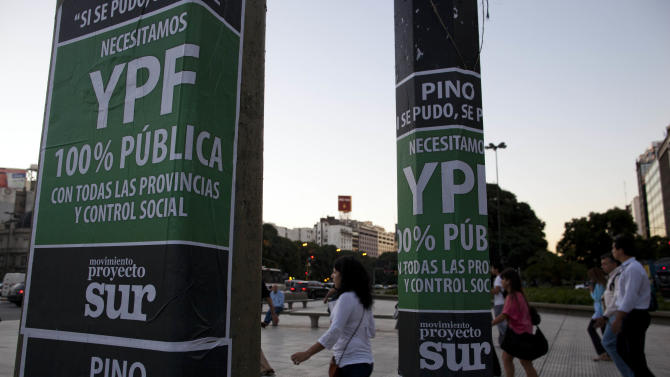 """People walk past signs reading in Spanish """"YPF, 100 percent public"""" in Buenos Aires, Argentina, Thursday April 19, 2012. Argentina's government showed no signs of backing down Thursday from expropriating a Spanish company's controlling stake in YPF, Argentina's formerly state-owned energy company, shrugging off international condemnation while finding overwhelming support for the plan in congress. (AP Photo/Natacha Pisarenko)"""