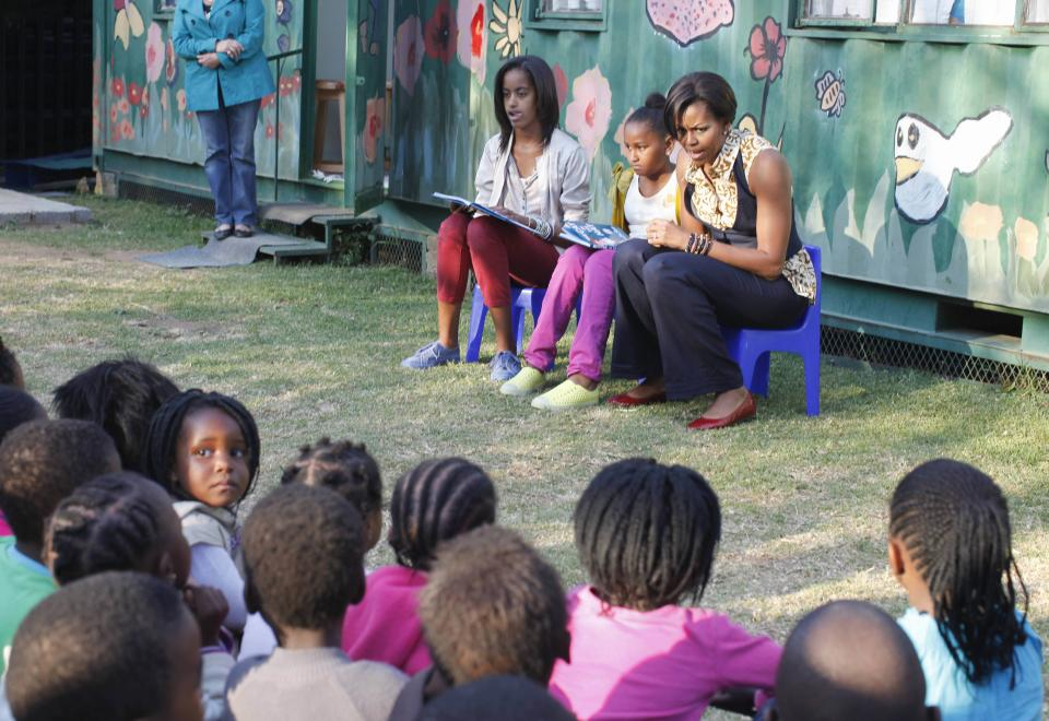 "First lady Michelle Obama, with daughters Malia, left, and Sasha, center, read from ""The Cat in the Hat,"" by Dr. Seuss, during their visit to the Emthonjeni Community Center in Zandspruit Township, Johannesburg, South Africa, Tuesday, June 21, 2011. (AP Photo/Charles Dharapak, Pool)"