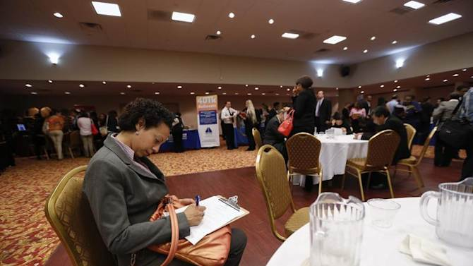 Woman fills out a job application as she attends a job fair in New York