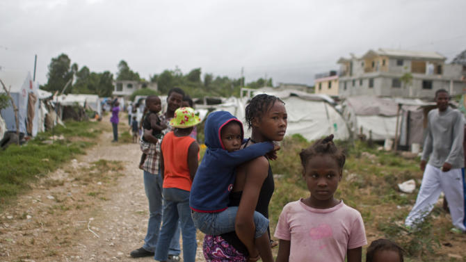 Children stand in a tent camp for people displaced by the 2010 earthquake ahead of the arrival of Tropical Storm Isaac in Port-au-Prince, Haiti, Friday Aug. 24, 2012. Tropical Storm Isaac strengthened slightly as it spun toward the Dominican Republic and vulnerable Haiti on Friday, threatening to bring punishing rains but unlikely to gain enough steam to strike as a hurricane. (AP Photo/Dieu Nalio Chery)