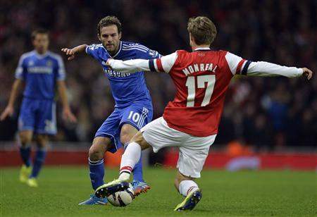 Arsenal's Monreal challenges Chelsea's Mata during their English League Cup fourth round soccer match at Emirates Stadium in London