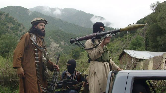 FILE - In this Sunday Aug. 5, 2012 file photo, Pakistani Taliban patrol in their stronghold of Shawal in the Pakistani tribal region of South Waziristan. Five years after setting up an umbrella organization to unite a violent symphony of militant groups operating in Pakistan's tribal regions, the Pakistani Taliban is fractured, strapped for cash and losing the support of a local population that is frustrated by a protracted war that has forced thousands out of their homes, say analysts and residents of the area. (AP Photo/ Ishtiaq Mahsud, File)