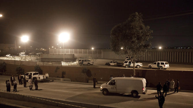 Mexican police and forensic experts examine the scene after a US border patrol agent shot and killed a man at the US-Mexico border in Tijuana, Mexico, late Tuesday June 21, 2011. Two men, presumably Mexican, assaulted two Border Patrol agents after crossing the border illegally about one mile west of San Diego's San Ysidro port of entry, a Border Patrol spokesman said. Tijuana police identified the victim as Jose Alfredo Yanez, 40. (AP Photo/Alejandro Cossio)