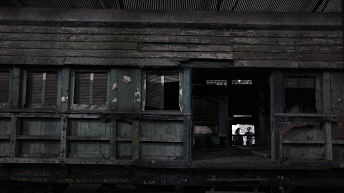Two men look at an abandoned railroad car once used by top Nigerian government officials in Lagos, Nigeria, on Saturday, April 13, 2013. The Nigerian Railway Corp., while recently restarting service from Lagos to the northern city of Kano, still has relics from the past littering the grounds of its headquarters in Lagos. Historians hope to preserve some of these old locomotives and train cars for future generations to see. (AP Photo/Jon Gambrell)