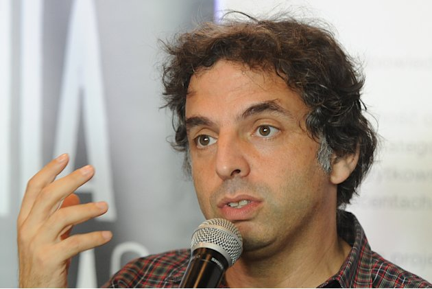 "Israeli writer  Etgar Keret speaks during a press conference one day ahead of the official opening of one of the world's narrowest houses, in Warsaw, Poland, Friday, Oct. 19, 2012. The two-level ""Kere"