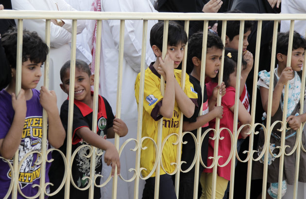 Saudi children watch Saudi men perform the traditional Arda dance, or War dance, during the Janadriyah Festival of Heritage and Culture on the outskirts of the Saudi capital Riyadh, Saudi Arabia, Friday, April 29, 2011.