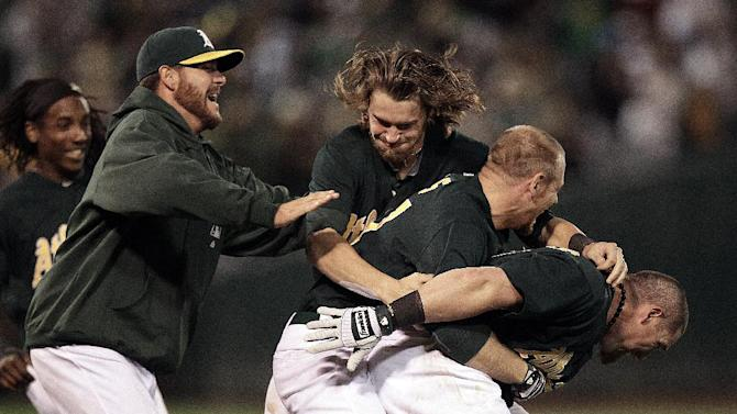 Oakland Athletics mob Brandon Moss, right, after Moss made the winning hit against the New York Yankees in the ninth inning of a baseball game Friday, July 20, 2012, in Oakland, Calif. (AP Photo/Ben Margot)