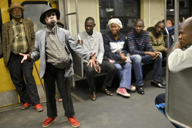 Two men dressed as former South African President Nelson Mandela travel on a train at Johannesburg's Park Station on their way to the Memorial Service for Mandela at the First National Bank Stadiu