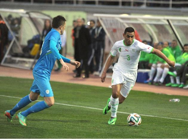 In this photo dated Wednesday, March 5, 2014, Algerian player, Ghoulam Faouzi Ghoulam, right, controls the ball while an unidentified Slovenian player looks on during their friendly soccer match at Bl