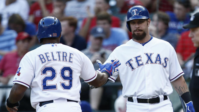Texas Rangers' Adrian Beltre (29) is congratulated by Josh Hamilton after scoring on a Mitch Moreland single against the Houston Astros during the first inning of a baseball game, Monday, Aug. 3, 2015, in Arlington, Texas. (AP Photo/Jim Cowsert)