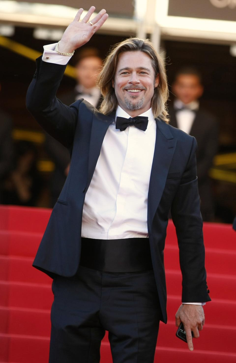 Actor Brad Pitt waves as he arrives for the screening of Killing Them Softly at the 65th international film festival, in Cannes, southern France, Tuesday, May 22, 2012. (AP Photo/Lionel Cironneau)