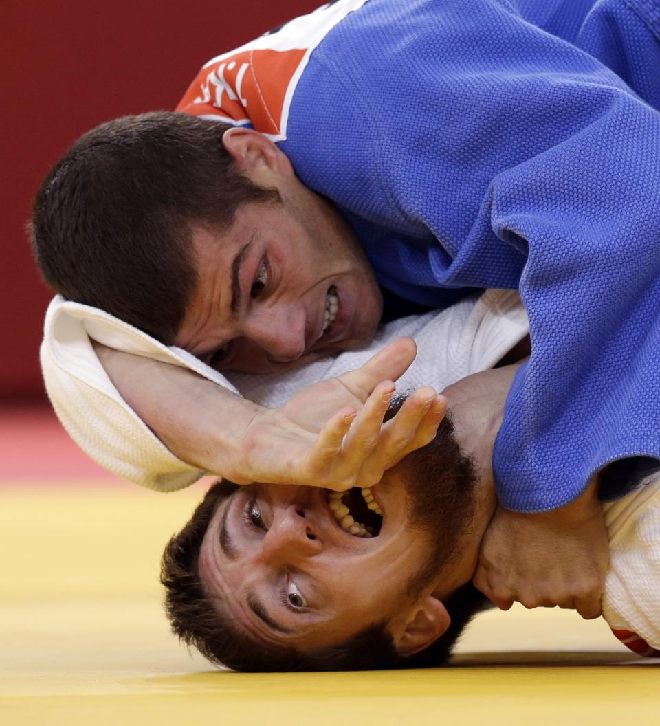 Tarlan Karimov of Azerbaijan (in blue) competes against Musa Mogushkov of Russia during the men's -66kg judo competition at the 2012 Summer Olympics, Sunday, July 29, 2012, in London. (AP Photo/Paul Sancya)