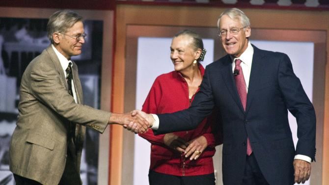 Jim Walton, left,, Alice Walton, center, and Robson Walton, right, greet each other during the beginning of the Walmart Stores Inc. shareholders' meeting in Fayetteville, Ark., Friday, June 1, 2012. The three siblings are the children of the late Sam Walton, founder of Walmart. (AP Photo/April L. Brown)